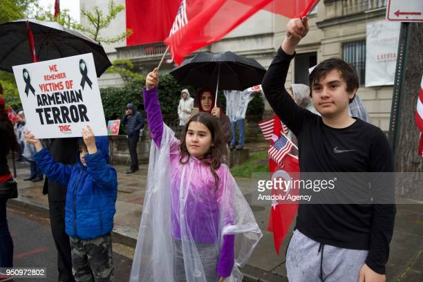 A child holds a banner reading We Remember The Victims Of Armenian Terror as other children wave a Turkish and an US flag during a demonstration in...