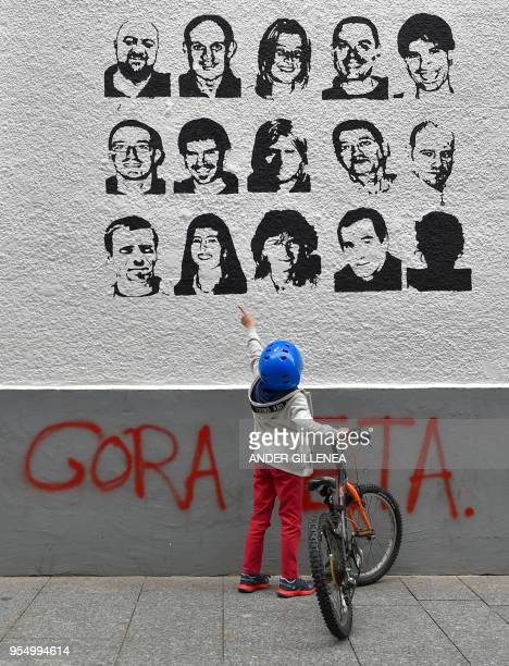 A child holds a bike while pointing at some portraits of Basque separatist group ETA prisoners next to a graffiti meaning Long life ETA in the...