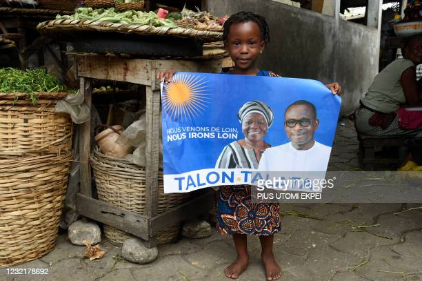 Child holds a campaign poster with photographs of incumbent Benin President Patrice Talon and running mate Mariam Talata at the market in Cotonou on...