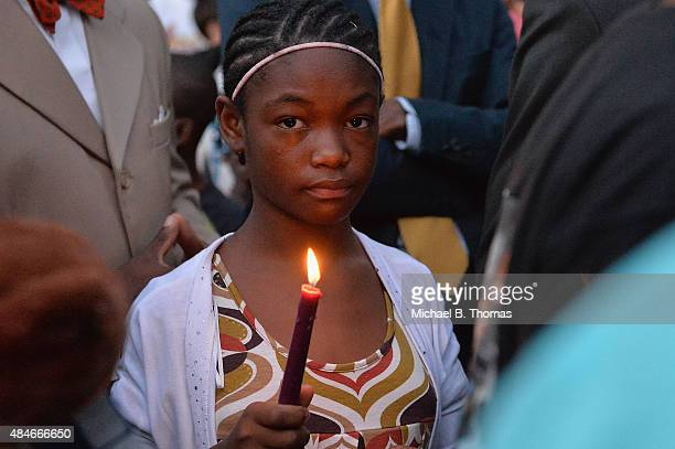 A child holds a candle during a candlelight vigil held in honor of Jamyla Bolden on August 20 2015 in Ferguson Missouri Jamyla Bolden was allegedly...