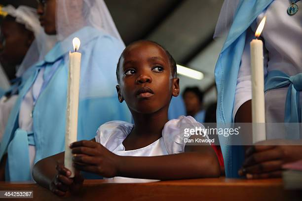 A child holds a candle during Sunday service on a national day of prayer for Nelson Mandela at Regina Mundi Church in Soweto on December 8 2013 in...