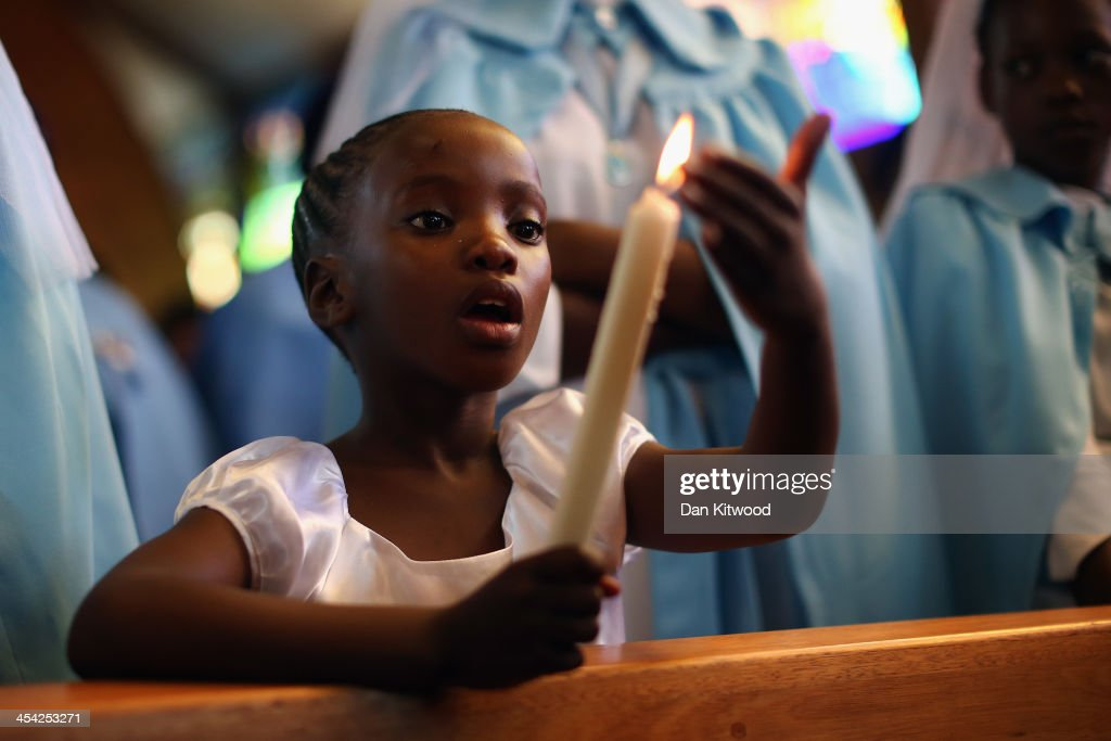 A child holds a candle during Sunday service on a national day of prayer for Nelson Mandela at Regina Mundi Church in Soweto on December 8, 2013 in Johannesburg, South Africa. Mandela, also known as Madiba, passed away on the evening of December 5th, 2013 at his home in Houghton at the age of 95. Mandela became South Africa's first black president in 1994 after spending 27 years in jail for his activism against apartheid in a racially-divided South Africa.