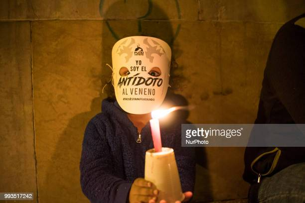 A child holds a candle in protest of the activists killed since the signing of peace agreements in Colombia Bogota on July 6 2018