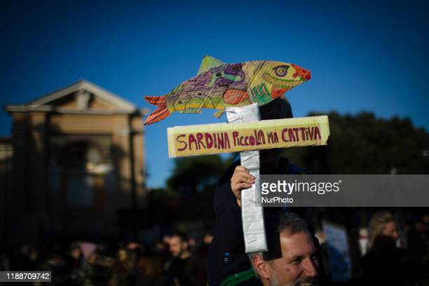 "Child holds a cardboard reading 'little bad sardina' during a demonstration of the ""Sardine Movement"", formed to oppose the far-right..."