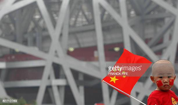 A child holds a Chinese flag in front the National Stadium also known as the 'Bird's Nest' ahead of the 2008 Beijing Olympic Games opening ceremony...
