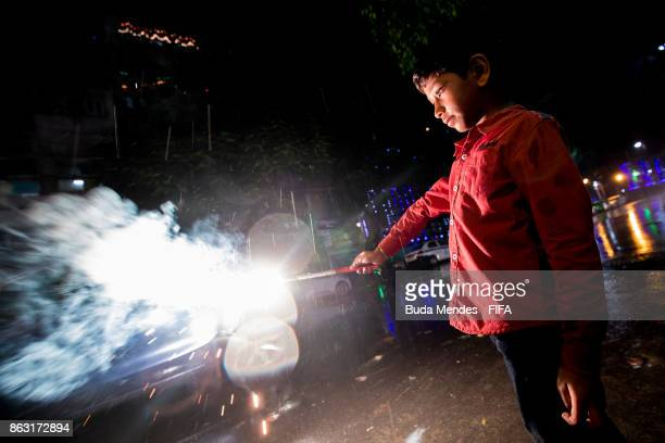 A child holds a firecracker while celebrating the Hindu festival of Diwali the annual festival of lights in India during of the FIFA U17 World Cup...