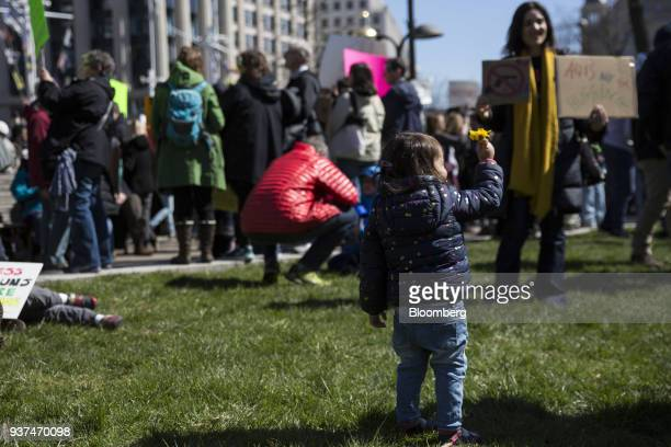 A child holds a flower on Pennsylvania Avenue during the March For Our Lives in Washington DC US on Saturday March 24 2018 Thousands of high school...