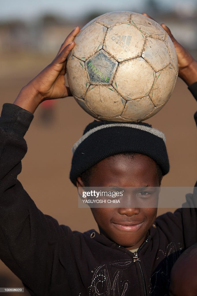 A child holds a football in Soweto on Ju