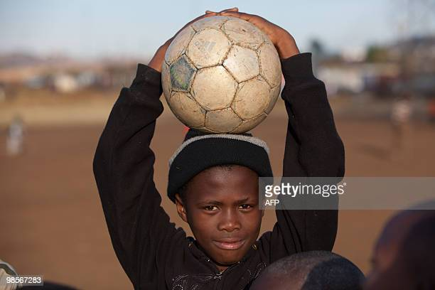 d4dfaadbb657 A child holds a football in Soweto on June 12 2009 two days ahead of the