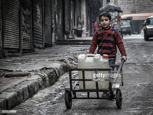 A child holds a gallon of water wells on the bandwagon in Aleppo Syria on December 30 2014