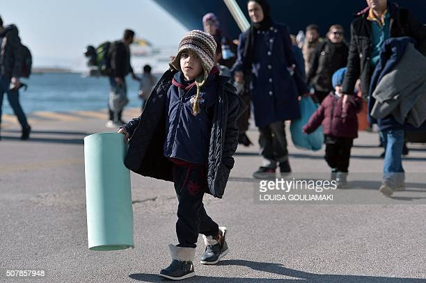A child holds a ground sheet as thousands of migrants and refugees arrive in the port of Piraeus from the Greek islands of Lesbos and Chios on...