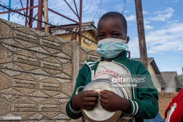 Child holds a metal pot before getting porridge on December 31, 2020 in Harare, Zimbabwe. Serving an average 2500 meals a day from her kitchen,...