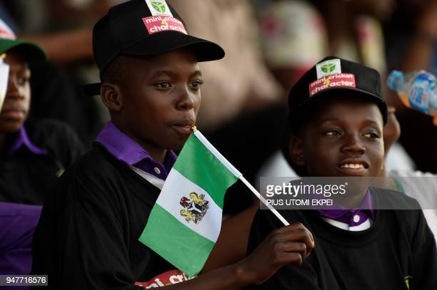 A child holds a Nigerian flag as he watches play during an International Cricket Council World Twenty20 African 'A' qualification match between...