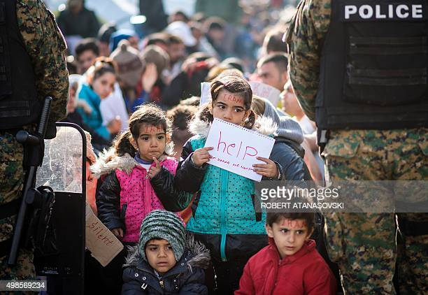 A child holds a notebook with a message reading 'help' as migrants and refugees from Iran sit on railway tracks while waiting to cross the...