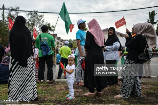 TOPSHOT A child holds a party flag outside a polling station during byelection in Port Dickson on October 13 2018 Anwar Ibrahim set his sights on a...