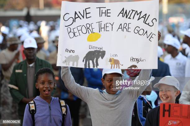 A child holds a placard as he takes part in a march to create awareness on protecting wildlife and nature as part of the Global March for Elephant...