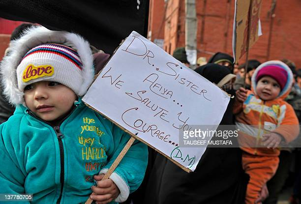 Child holds a placard during a demonstration by activists of right wing all-women Dukhtaran-E-Milat in Srinagar on January 27, 2012. Women protest...