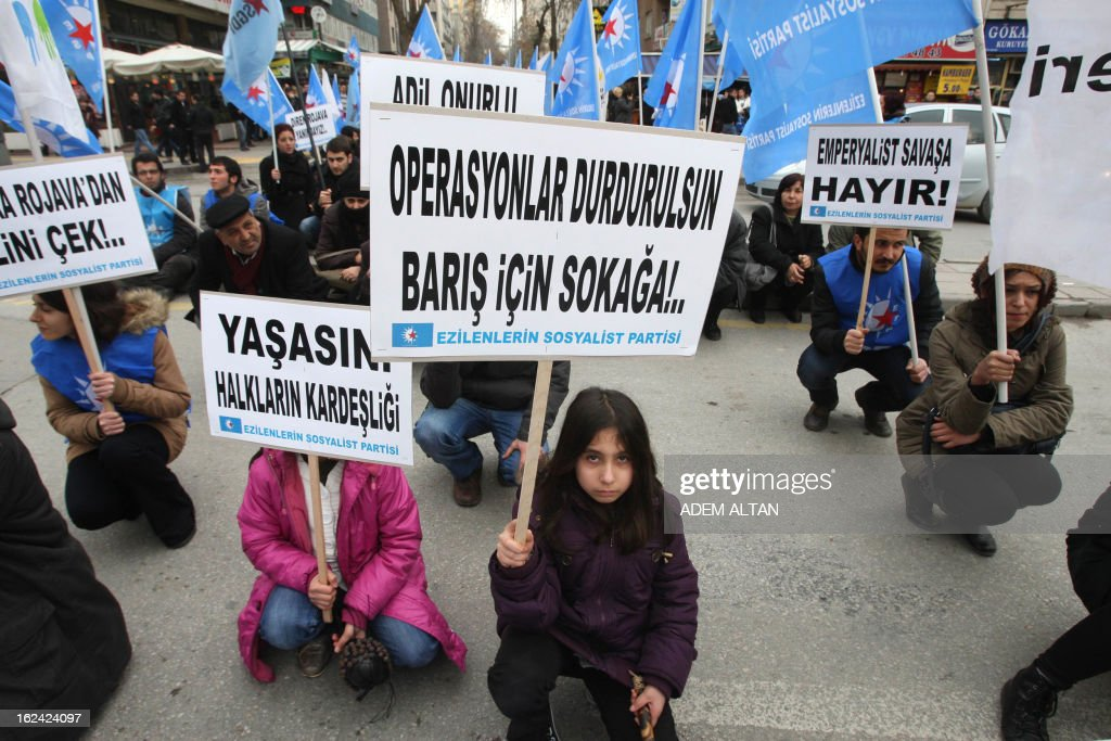 A child holds a placard during a protest of members of leftist political parties against NATO's Patriot missiles stationed near the border with Syria, in Ankara, on February 23, 2013.