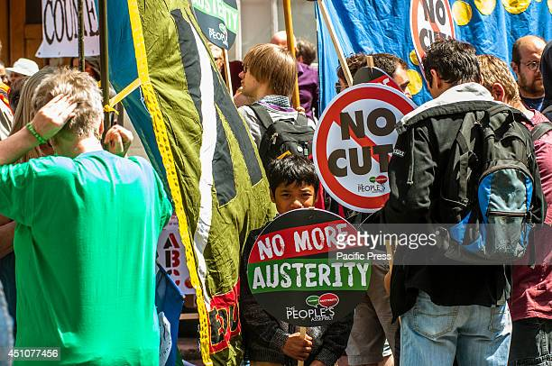 A child holds a placard during the protest that reads ' No more austerity' Protesters are asking for the scrapping of zero hour contracts the...