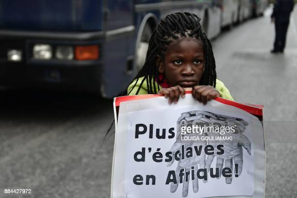 A child holds a placard reading 'No more slaves in Africa ' in front of police blockade during a demonstration of migrants on December 2 2017 in...