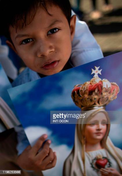 A child holds a poster as the image of the Virgin of Fatima arrives from Portugal to the Cathedral in Managua on January 25 2020