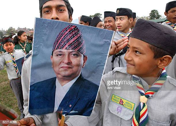 Child holds a poster of King Gyanendra as thousands of people arrive to celebrate Democracy Day and to greet the Queen Komal who was marking her 55th...