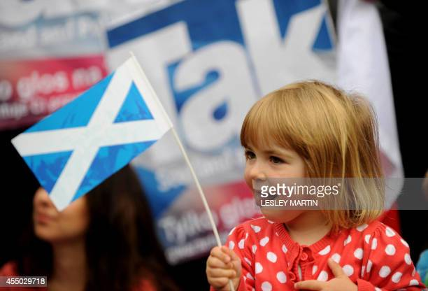 A child holds a Scottish flag during a photocall with Scottish First Minister Alex Salmond and European citizens to celebrate European citizenship...