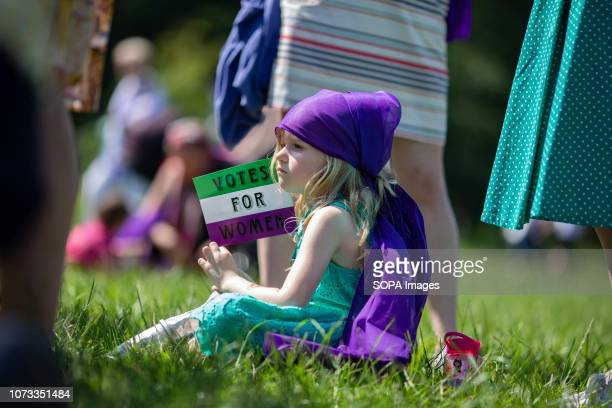 A child holds a sign that reads 'Votes for Women' at a march organised as a tribute to the suffragette movement and to mark the 100 year anniversary...
