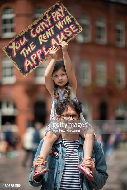 """Child holds a sign which says """"you can't pay the rent with applause"""" during a protest on July 3, 2021 in Cardiff, United Kingdom. On July 05, 1948..."""