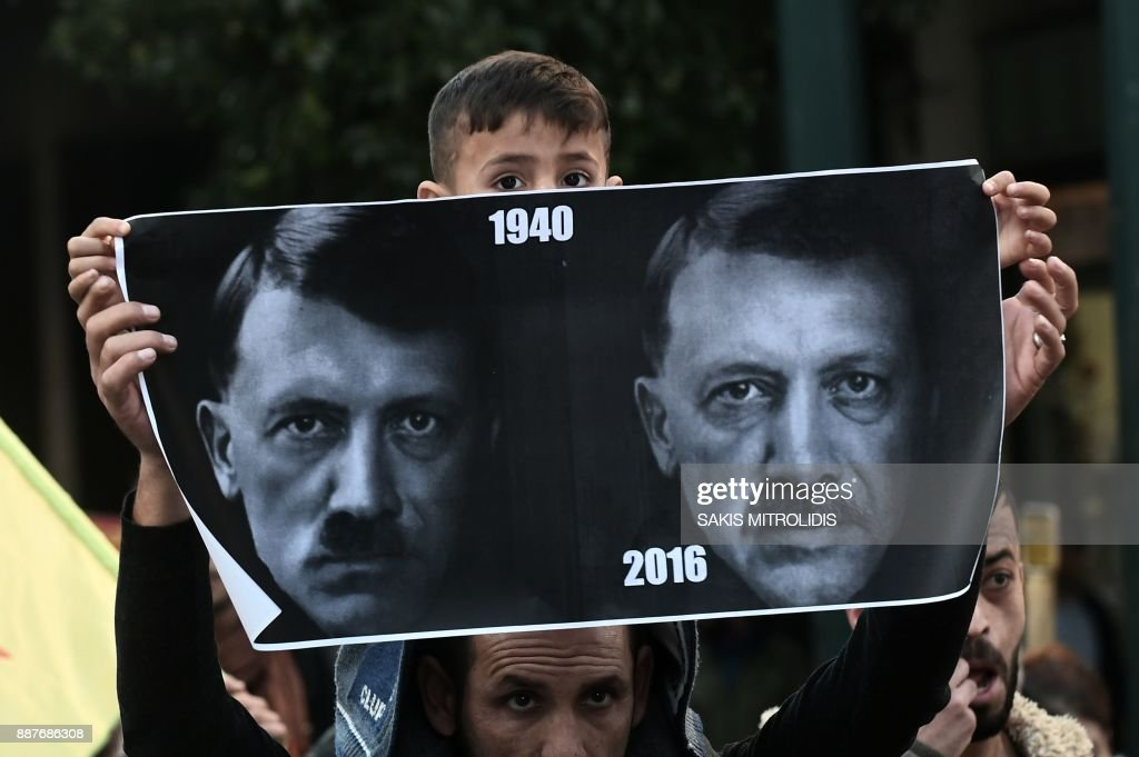 A child holds a sign with portraits of Turkish President Recep Tayyip Erdogan and German dictator Adolph Hitler as members of the Kurdish minority living in Greece demonstrate against the visit of the Turkish president in central Athens on December 7, 2017. Turkey's president began a state visit to Greece on December 7, the first by a Turkish head of state in 65 years, by needling his hosts with revisionist border talk and complaints about its treatment of Muslims. /