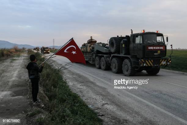 A child holds a Turkish flag as Turkish Armed Forces' military vehicles are being transported to border units of Turkey's Reyhanli Kirikhan and Hassa...