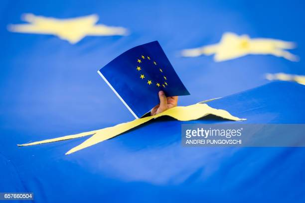 TOPSHOT A child holds an EU flag through a 'wind vent' hole of a huge EU flag banner during a pro Europe rally on March 25th in Bucharest Romania /...