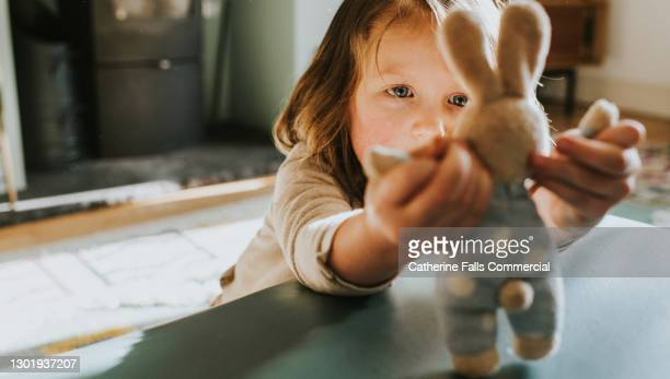 child holds and studies a small toy bunny - individuality stock pictures, royalty-free photos & images
