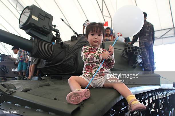 A child holds balloon on top of a tank during the National Children's Day at the Horse Brigade Bangkok Weapons such as tanks troop transport...