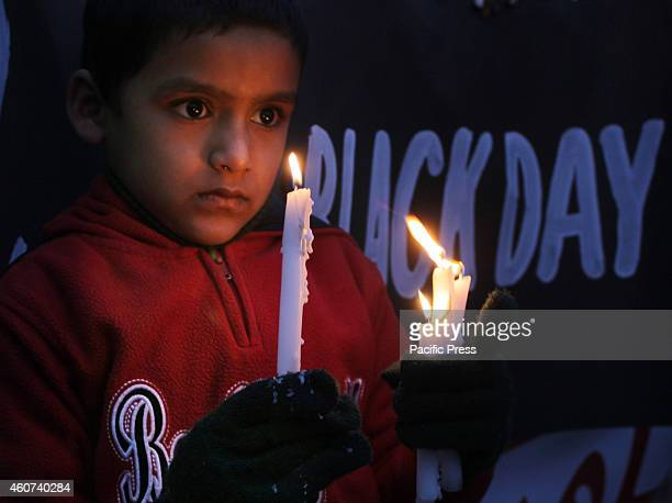 A child holds candles to pay tribute to the victims killed in Tuesday's Taliban attack on a militaryrun school in Peshawar in Lahore At least 148...
