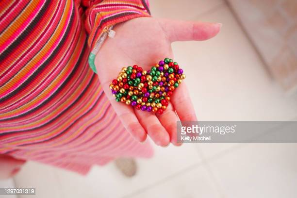 child holds colourful heart shape arts and crafts - embellished dress stock pictures, royalty-free photos & images