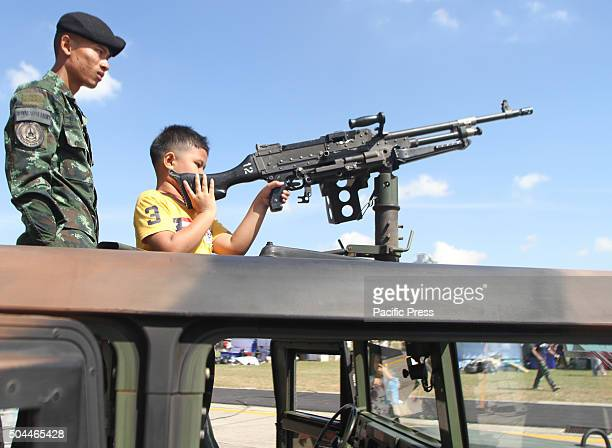 A child holds gun during the National Children's Day at the Horse Brigade Bangkok Weapons such as tanks troop transport artillery guns helicopter are...
