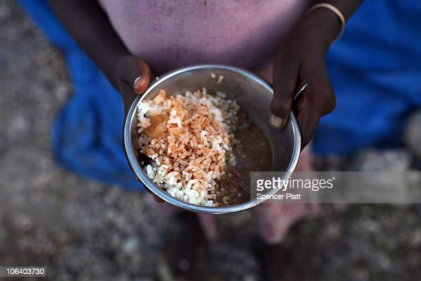 A child holds her dinner in a tent camp for individuals who have lost their homes in the January 12 earthquake in Cite Soleil a historically...