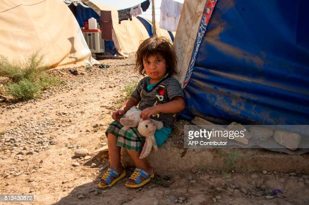 A child holds his teddy bear and sits next to a tent at a UNHCR refugee camp in Hammam alAlil on the outskirts of Mosul on July 12 2017 Iraqi Prime...