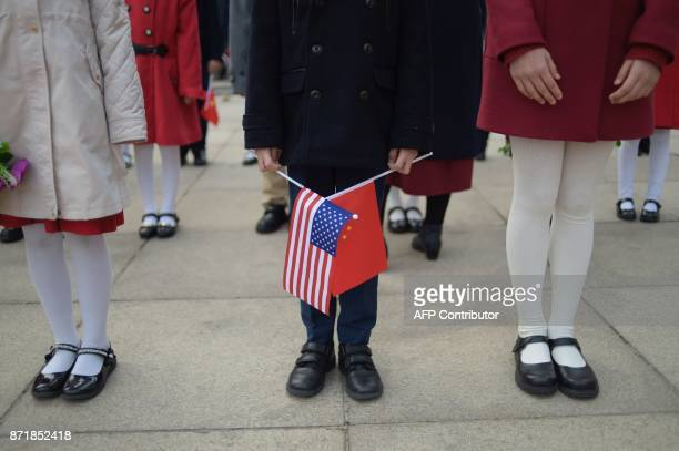 A child holds national flags during a welcome ceremony for China's President Xi Jinping and US President Donald Trump at the Great Hall of the People...