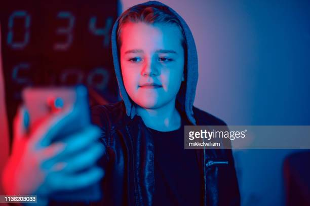 Child holds phone for photo or video shoot of himself at night