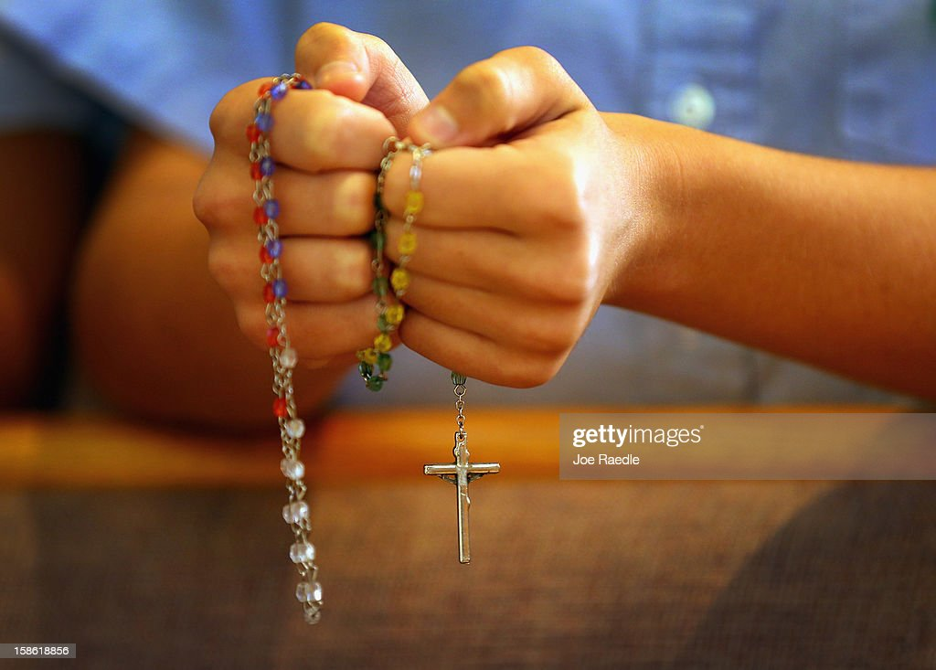 A child holds rosary beads as she prays during a service at St. Rose of Lima School, for the victims of the school shooting one week ago in Newtown, Connecticut on December 21, 2012 in Miami, Florida. Across the country people marked the one week point since the shooting at Sandy Hook Elementary School in Newtown, Connecticut that killed 26 people.