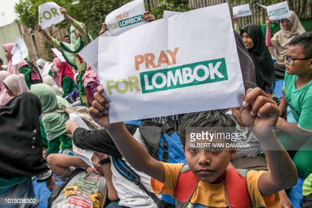 A child holds up a placard that reads 'pray for Lombok' during an earthquake evacuation drill in Medan on the western Indonesian island of Sumatra on...
