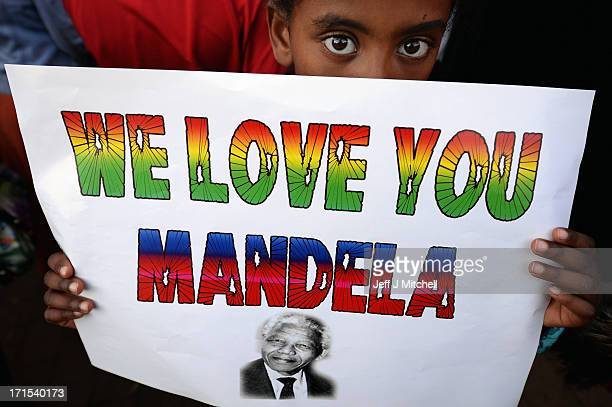A child holds up a sign in support of former South African President Nelson Mandela outside the Mediclinic Heart Hospital June 26 2013 in Pretoria...