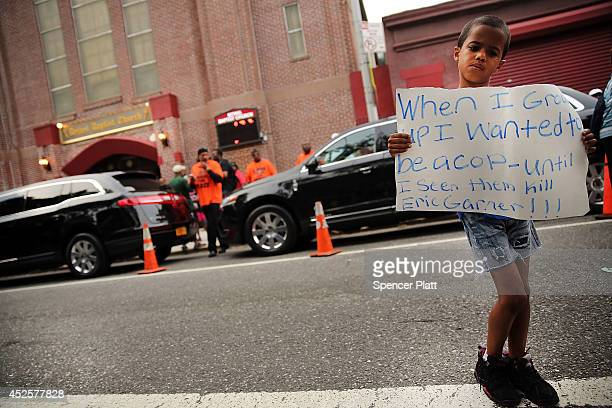 A child holds up a sign outside of the Bethel Baptist Church before the funeral for Eric Garner on July 23 2014 in New York City New York Mayor Bill...