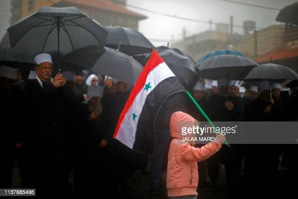 TOPSHOT A child holds up a Syrian national flag as residents of the Israeliannexed Golan Heights hold a rally under the rain in the Druze village of...