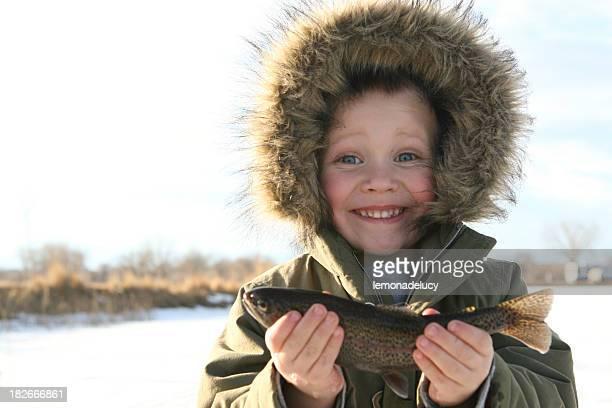 child ice fishing holding up his fish
