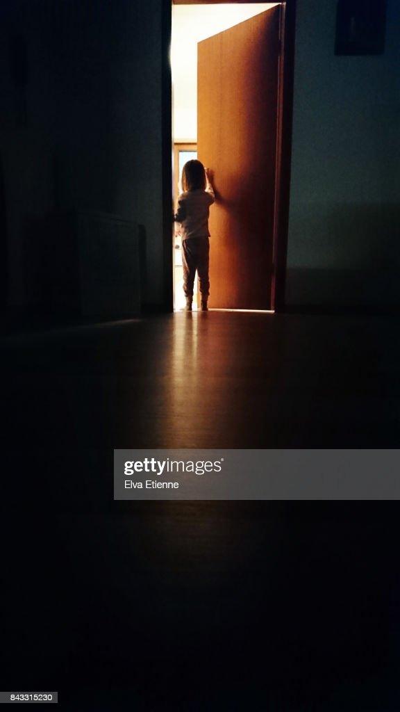 Child in a dark hallway, opening a door into the light : Stock-Foto