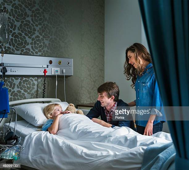 Child in a hospital bed with parents next to her.