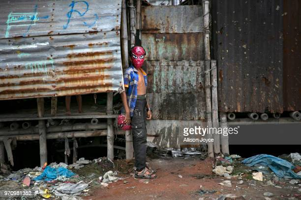 A child in a mask stands next to a polluted canal that leads to the Buriganga river in Shyampur June 10 2018 in Dhaka Bangladesh Bangladesh has been...